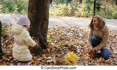 mother and daughter playing together in the autumn park...