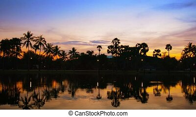 Sunset behind Trees with Shadowy Pond in Foreground - Video...