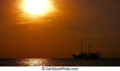 Pirate Ship Tour Boat at Anchor off Patong Beach, Thailand, at sunset.