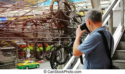 Photographer shooting messy, spaghetti-like wires over an...