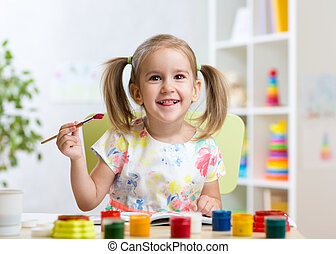 kid painting at home or day care center - smiling kid girl...