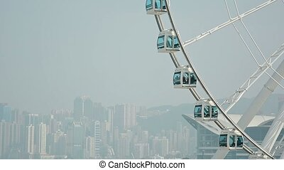 Huge Ferris Wheel Rotates Slowly against a Cityscape...