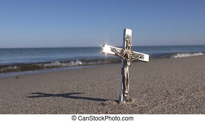 Seascape with religion symbol crucifix in the sand