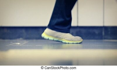 Many Peoples Feet Passing By on a Polished Cement Floor -...