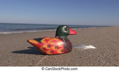 decorative wooden duck on beach - Seascape with decorative...