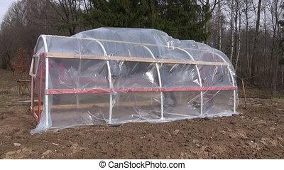 Workers building greenhouse - Men gardener covering...