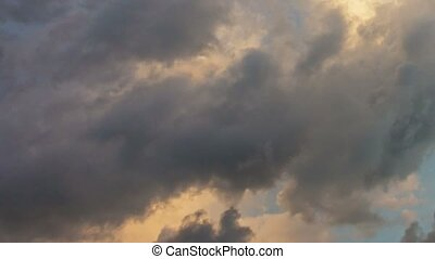 Fluffy Clouds Drifting across the Sky in the Fading Light -...