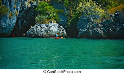 Kayakers Exploring a Rocky Inlet along a Tropical Coastline...