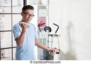 Mature Asian man with dumbbells at gym