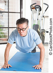Mature Asian man pushup at gym - Portrait of active 50s...