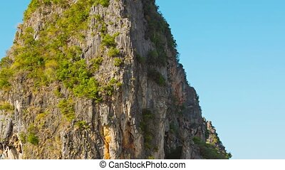 Huge Limestone Rock Towering over a Tropical Beach in...