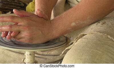 potter molds clay small pot - potter sculpts clay small pot