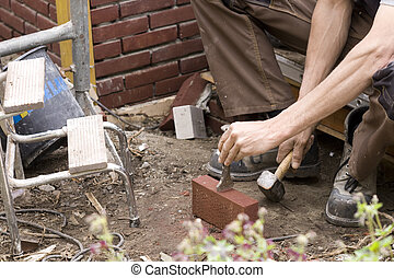 Bricklayer at work - Bricklayer breaking a brcik on site