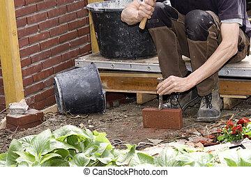 Bricklayer breaking a brick in garden