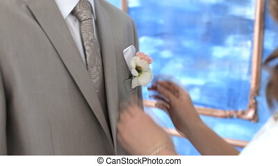 bride groom straightens boutonniere closing up