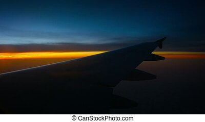 Aerial View of an Airplanes Wing over the Horizon at Sunset...