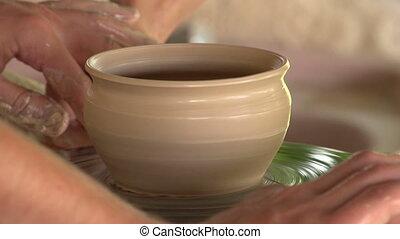 potter sculpts clay small pot