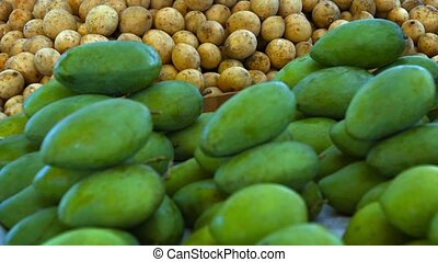 Small, Green Mangoes and Lanzones Fruit at a Public Market -...