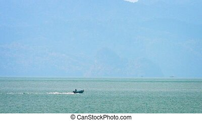 Small Motorboat Cruising Toward the Seacliffs of a Tropical...