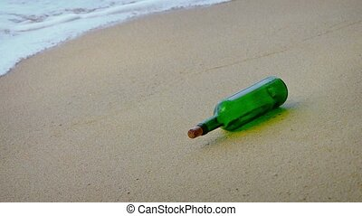 Green glass wine bottle rolls in the gentle waves on a sandy...