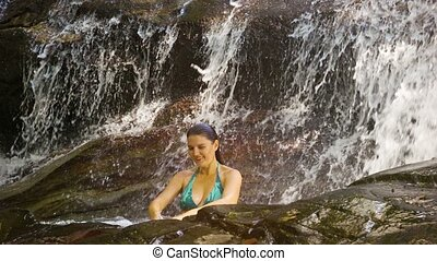 Young woman bathing in a natural waterfall