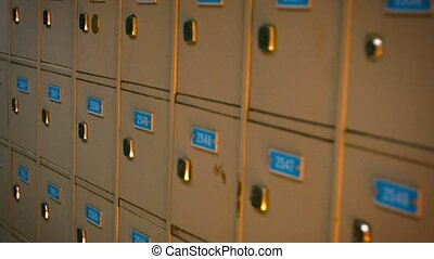Row of identical, gray painted old post office boxes with...