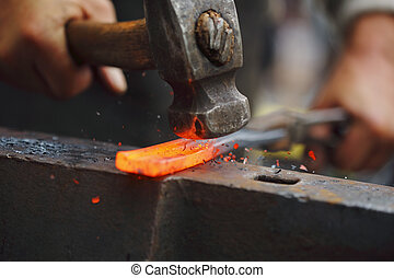 Forging hot iron - Detail shot of hammer forging hot iron at...