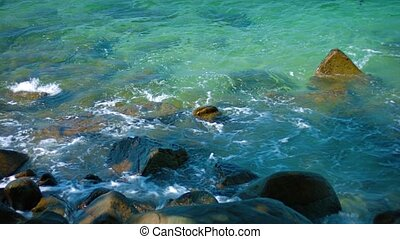 Gentle Waves Wash over Boulders on a Tropical Beach in...
