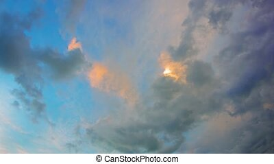 Puffy Clouds Drifting across the Sky in the Fading Light -...