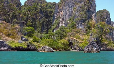 Limestone Cliffs Towering over a Rocky Tropical Beach -...