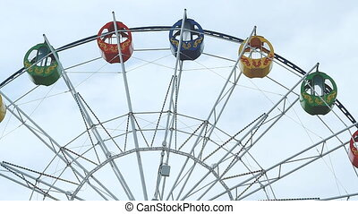 view of a ferris wheel over blue sky - Underside view of a...