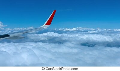 Flying over Layer of Clouds from Airplane Window - Dramatic...