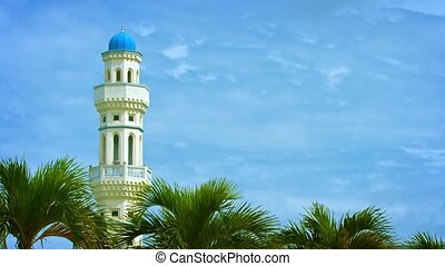 Single Minaret of a Mosque with Palm Trees in the Foreground...