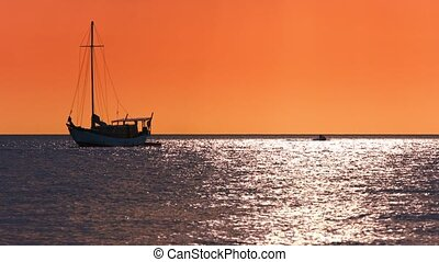 Sailboat Riding at Anchor under an Orange Sunset Sky -...