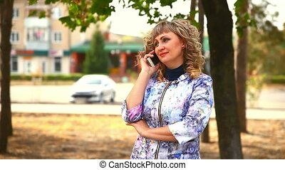 full fat middle-aged woman on the phone in the park behind the cars drive lifestyle
