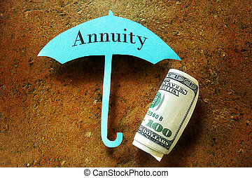 Annuity concept - Hundred dollar bill under a paper umbrella...