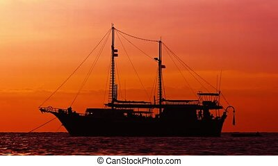 Beautiful Sailboat at anchor on a Tropical Sea at Sunset -...
