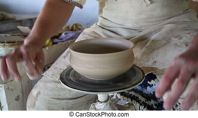 potter sculpts clay small pot
