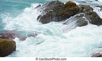 Ocean Waves Washing over Boulders on a Rocky, Tropical Beach...