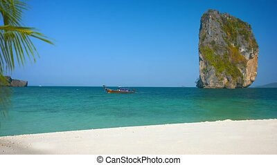 Motorized, Wooden Tour Boat Cruising past Railay Beach in Thailand