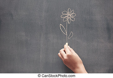Drawing flower - Woman drawing a flower on a blackboard