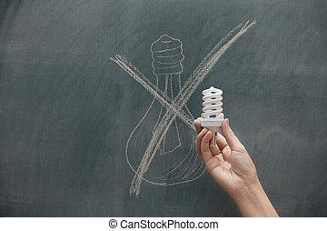 Energy saving - Human hand holding energy saving lamp at the...
