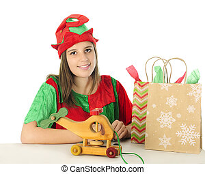 Elf Behind a Gift Table - A pretty teen elf smiling at the...
