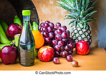 Bottles of juice and fruits on a table.