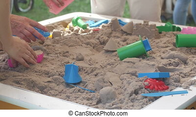 Children and adults playing in the sandbox