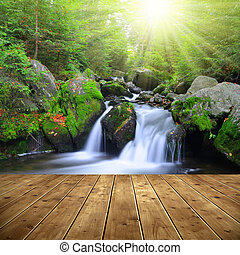 Waterfall on a mountain creek. In the foreground a wooden...