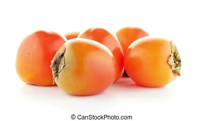Red ripe persimmons rotating over white background