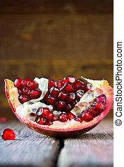 Open fresh ripe pomegranates fruit on wooden background