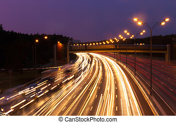 Highway at evening - Illuminated highway at evening with...