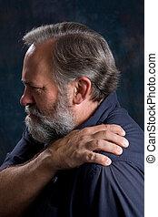 Painful Shoulder - Man massages his painful shoulder